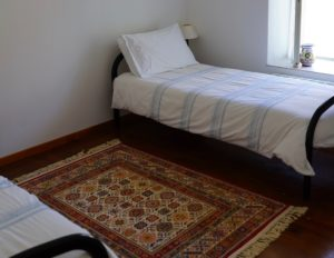 Two single beds in a room with a timber floor and rugs